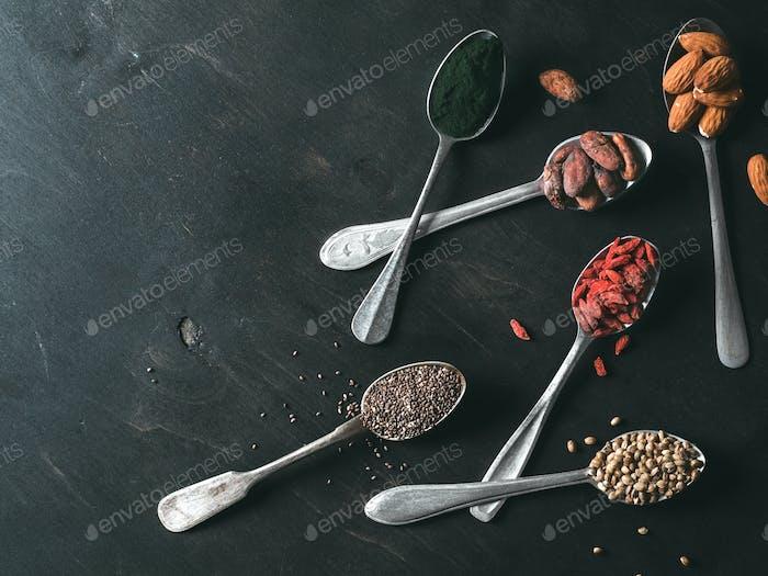 Löffel verschiedener Superfoods auf schwarzem Holztisch