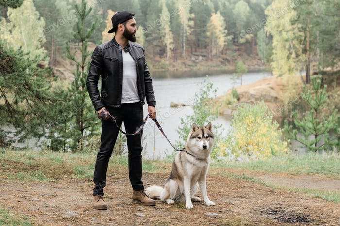 Young stylish man in black leather jacket and jeans holding leash of his pet