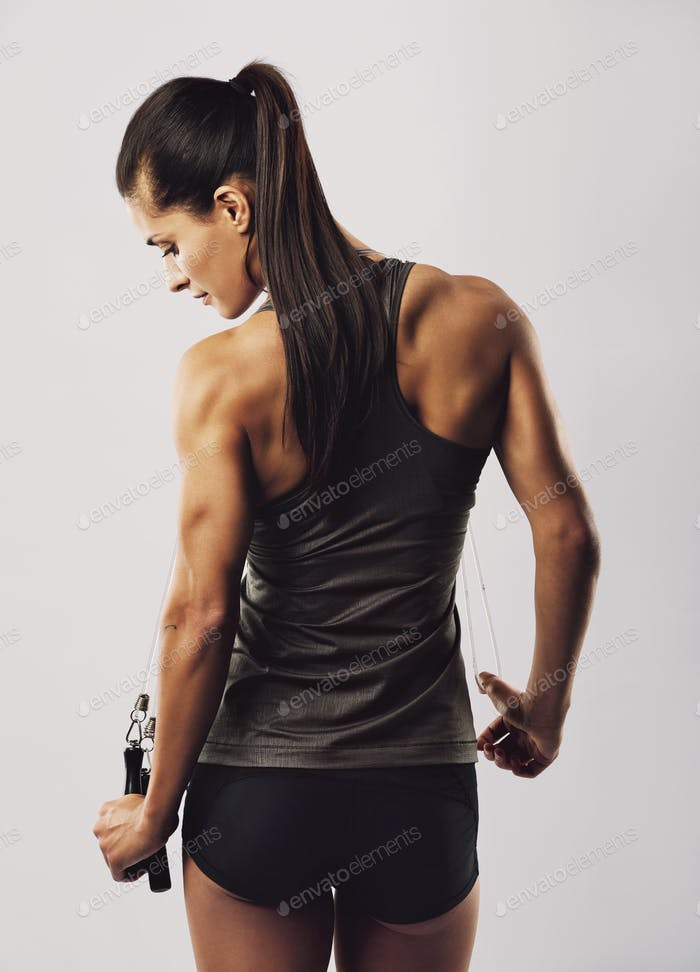 Female athlete with jumping rope posing on grey background