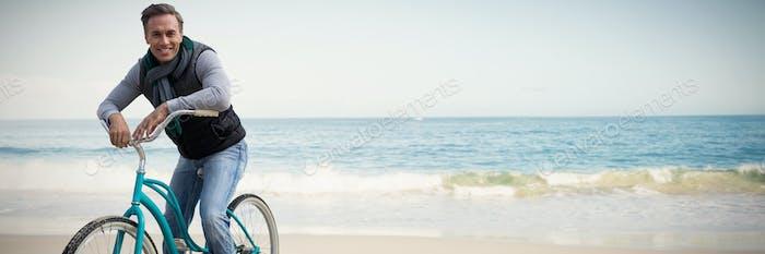 Composite image of digital composite of handsome man on a bike ride