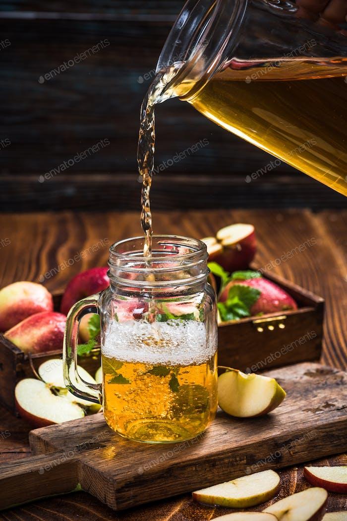 Gießen Sie frischen und gesunden Apfelsaft in Glas