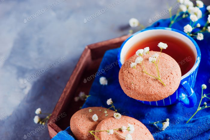 Morning scene with a small blue teacup and oatmeal cookies on a wooden tray with a blue linen napkin