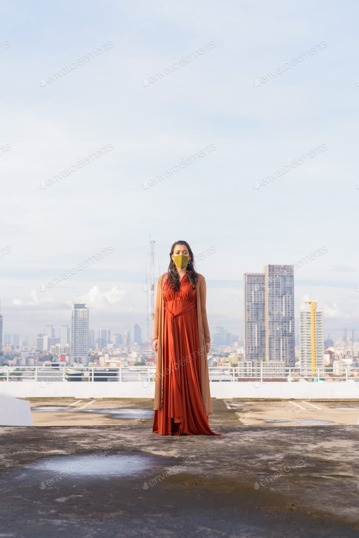 Full body shot of young Indian woman wearing mask against view of the city