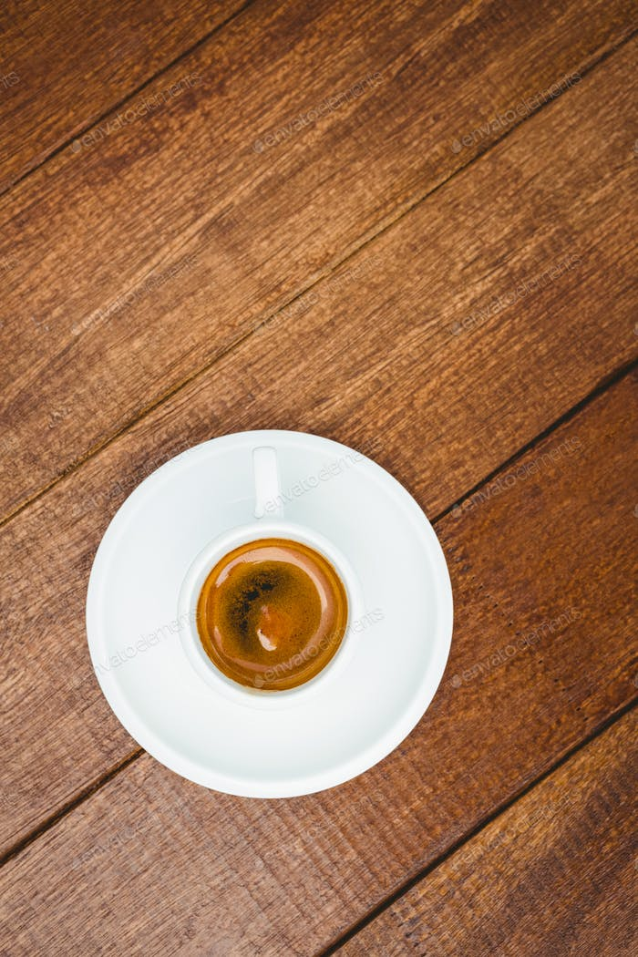 Above view of a coffee against wood desk