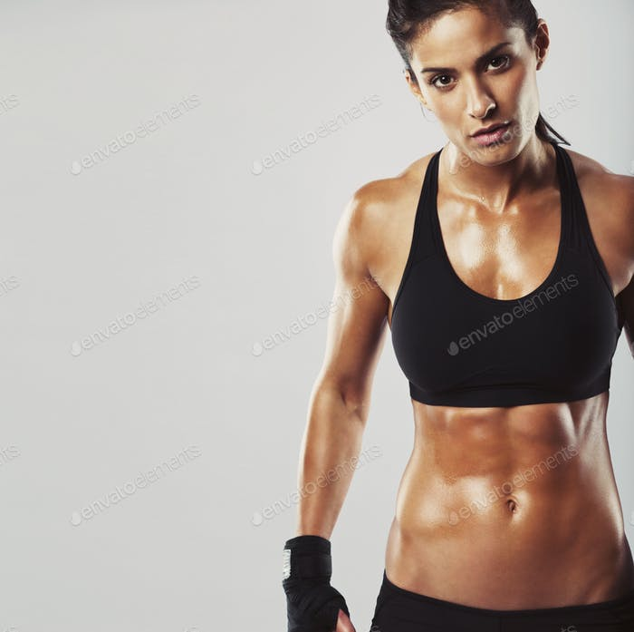 Female fitness model on grey background