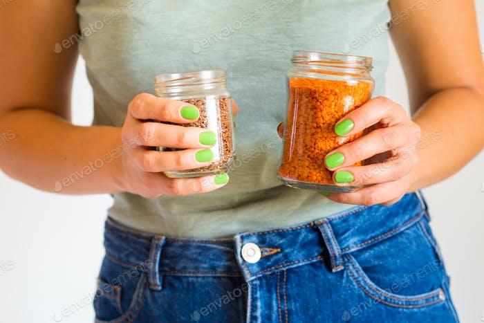 Woman buying lentils using glass jars. Zero waste