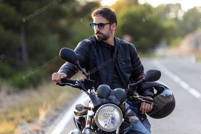 Handsome bearded biker looking to sideways while sitting on his motorbike and holding helmet.