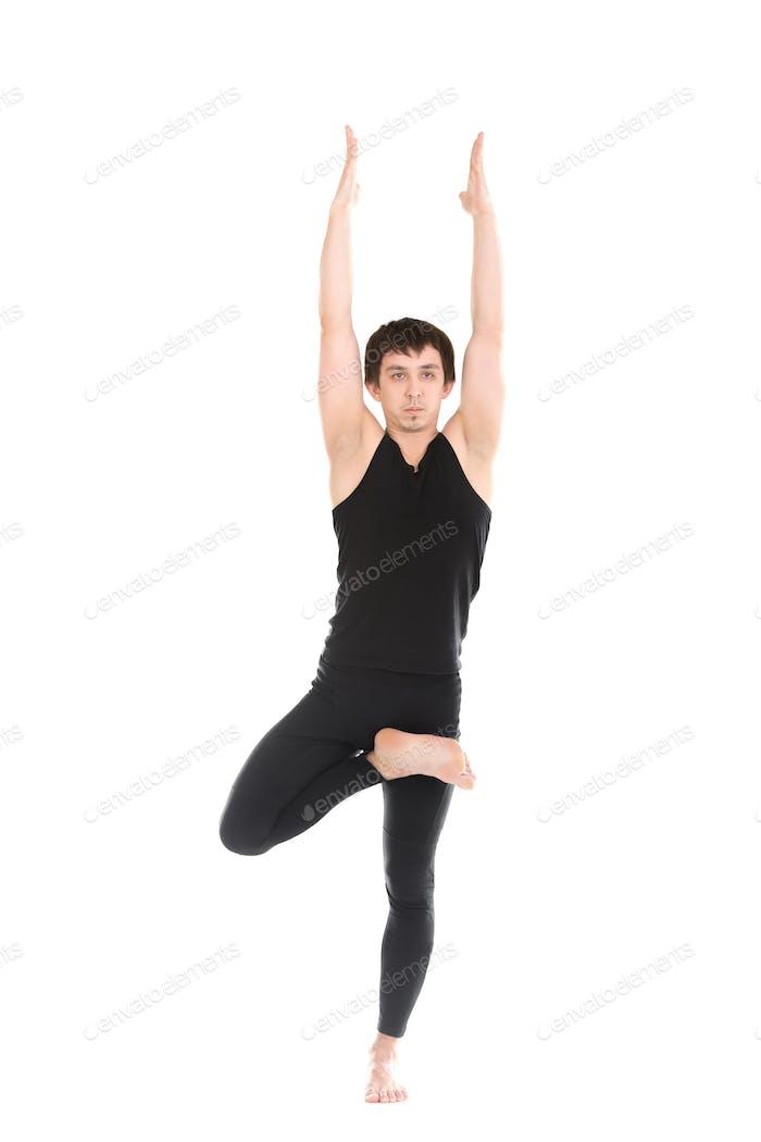 Sportlicher junger Mann stehend in Tree Pose