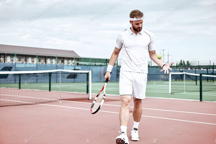 Portrait of young caucasian teenis player wearing tennis dress, walking on tennis hardcourt, summer
