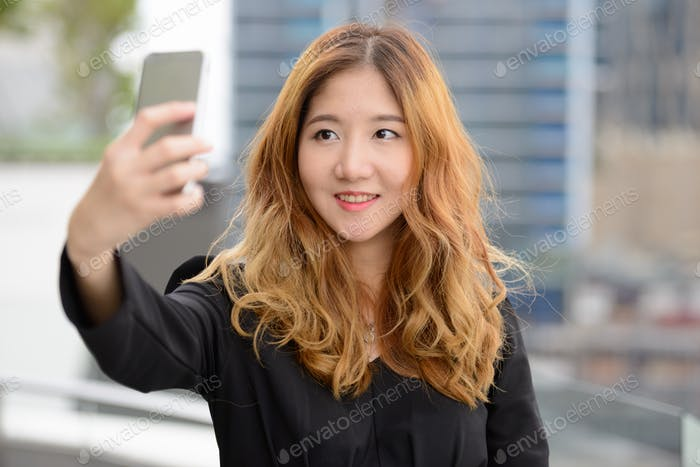 Thumbnail for Face of happy young Asian businesswoman taking selfie in the city