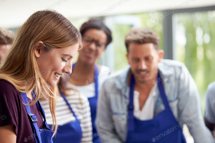 Students Watching Female Teacher Following Recipe In Cookery Class