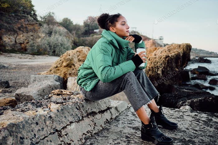 Beautiful African American girl in down jacket with cup to go dreamily sitting on stones by the sea