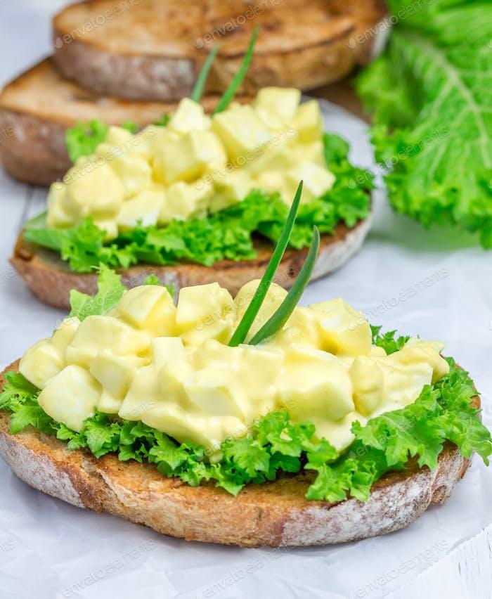 Eiersalat und Salat auf Nussbrot garniert mit grüner Zwiebel