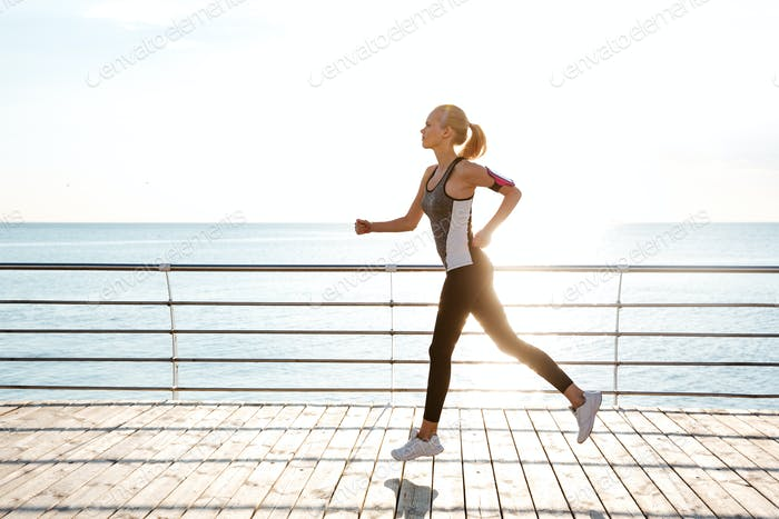 Beautiful young sportswoman training and running on pier