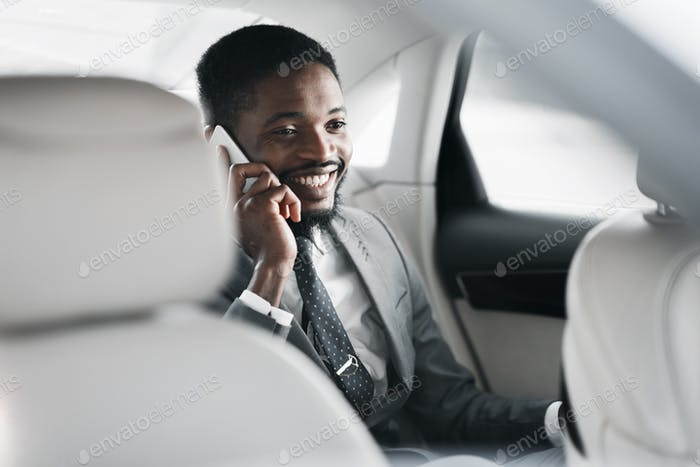 Successful businessman talking on phone in car