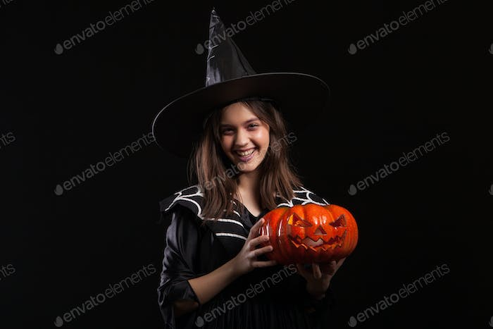 Cute little girl with a evil laugh doing sorcery with a pumpking for halloween
