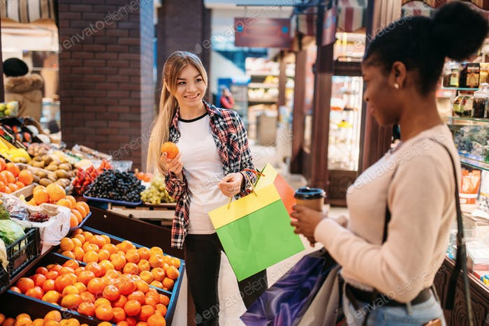 Black and white women buying fruits after shopping