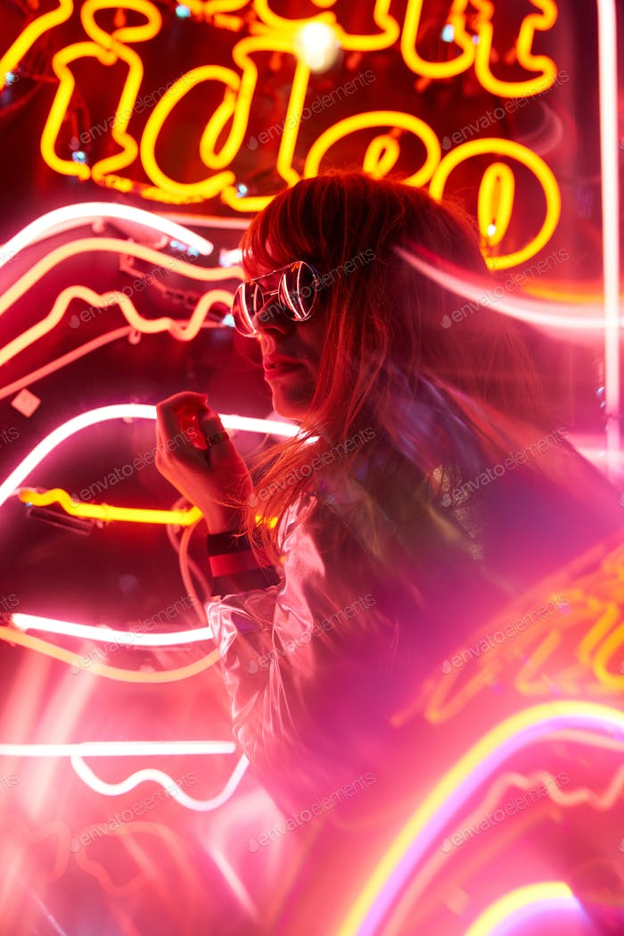 Portrait of woman with silver jacket and sunglasses in neon lights