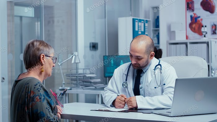 Physician consulting an elderly retired woman