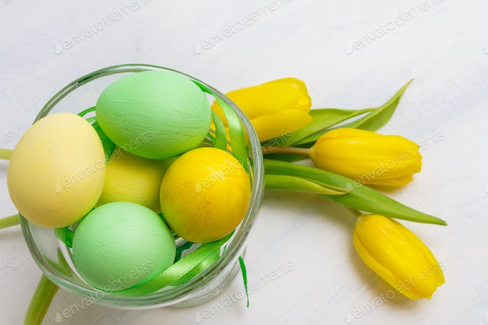 Easter table centerpiece with yellow tulips  and painted eggs in