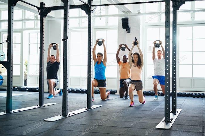 Diverse Gruppe von Fit-Menschen, die im Fitnessstudio trainieren