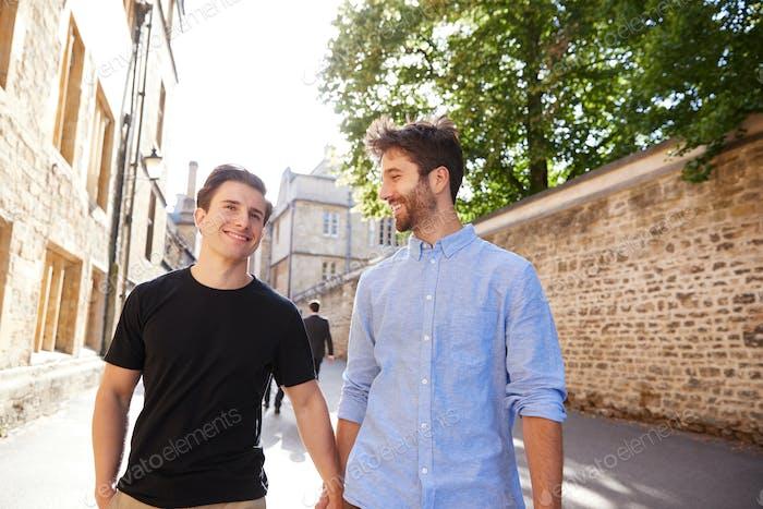 Liebevolle männliche Homosexuell Paar auf Urlaub halten Hände zu Fuß entlang Stadt Straße