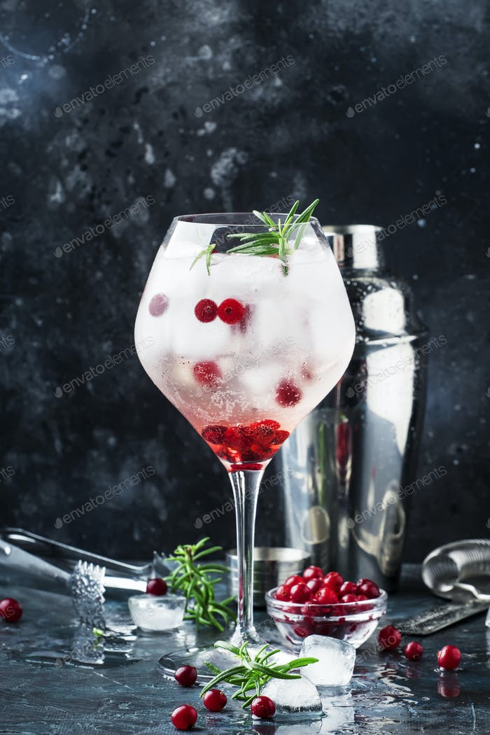 Cranberry cocktail with ice, fresh rosemary and red berries in big wine glass