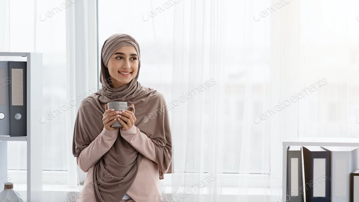 Arabische Geschäftsfrau mit Teetasse in den Händen, mit Pause im Büro