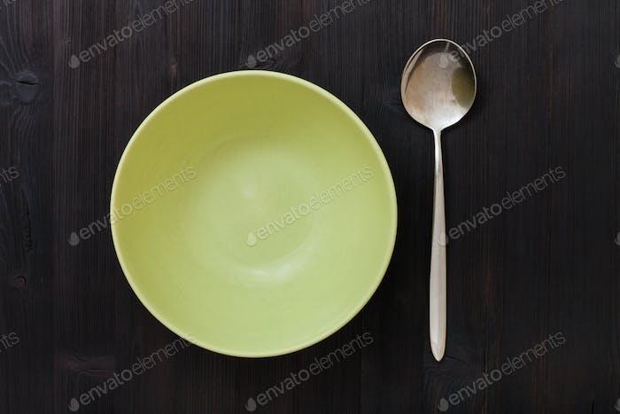 Draufsicht grüne Schüssel und Löffel auf dunkelbraunem Tisch