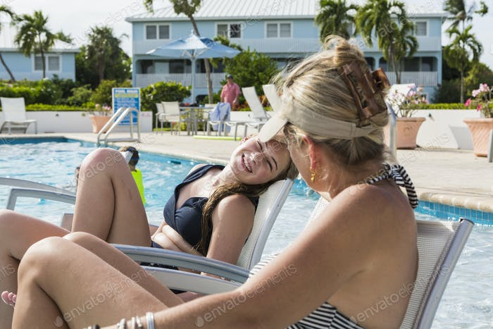 mother and her 13 year old daughter talking by the pool