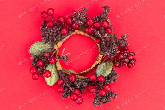 Beautiful round Christmas garland on red background.