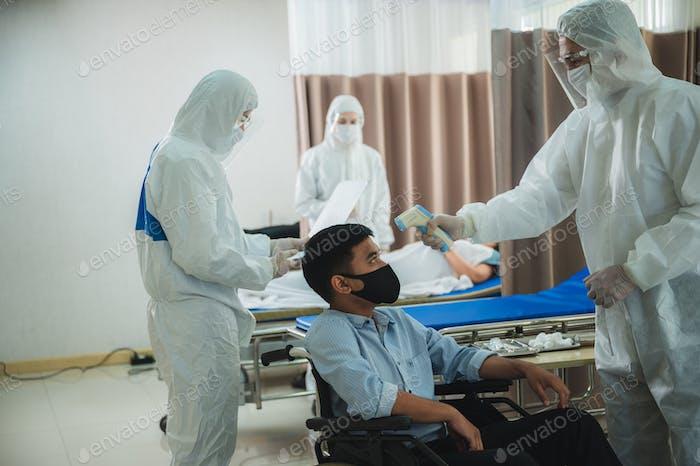 Fachärzte in den vollen Schutzanzügen und OP-Masken untersuchen