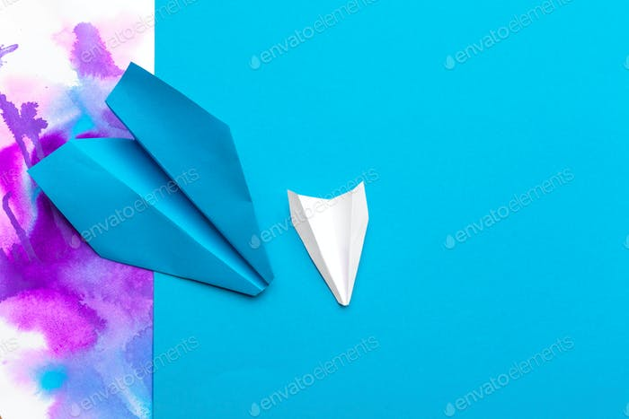 white paper airplane on a color block paper background