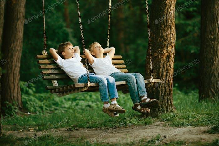 little boys dreaming on swing