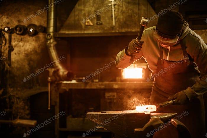 Blacksmith forging the molten metal on the anvil in smithy