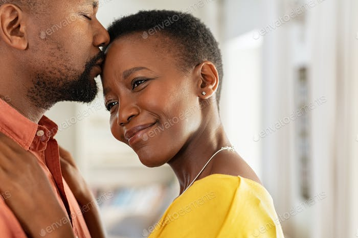 Black man kissing his wife on forehead