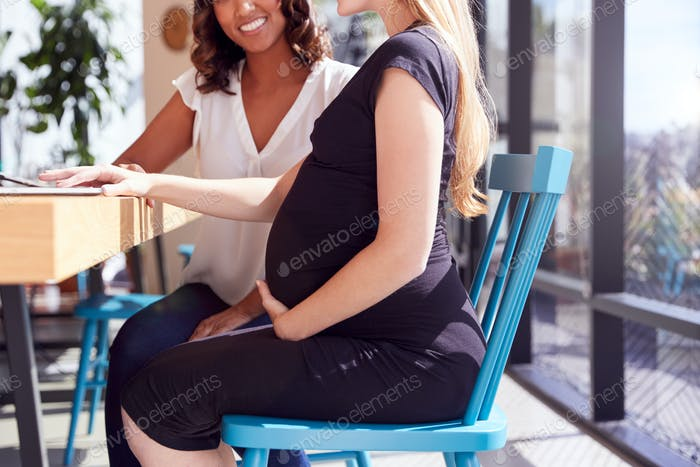 Close Up Of Businesswoman Using Laptop Working With Pregnant Female Colleague In Modern Office