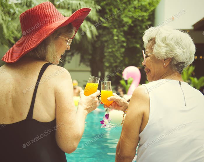Senior couple women with orange juice by the pool together