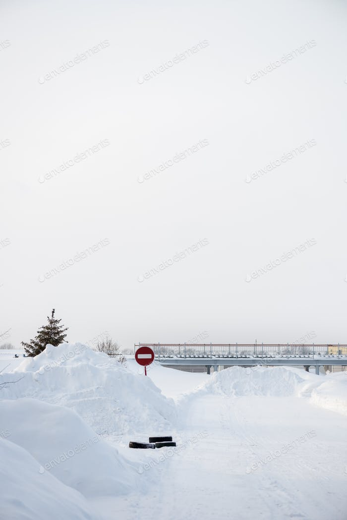 White Snowy Landscape with Road Sign