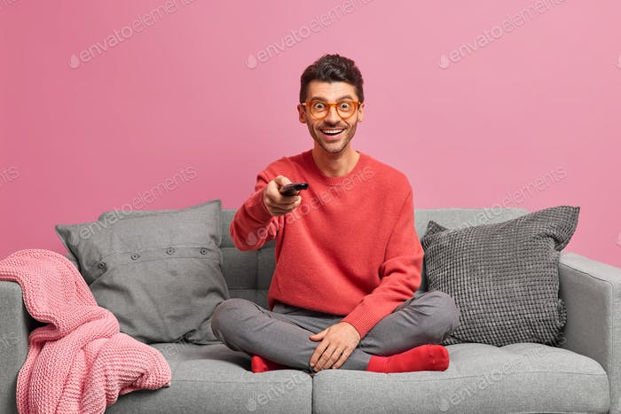 People home lifestyle leisure concept. Cheerful relaxed guy sits in lotus pose on comfortable sofa h