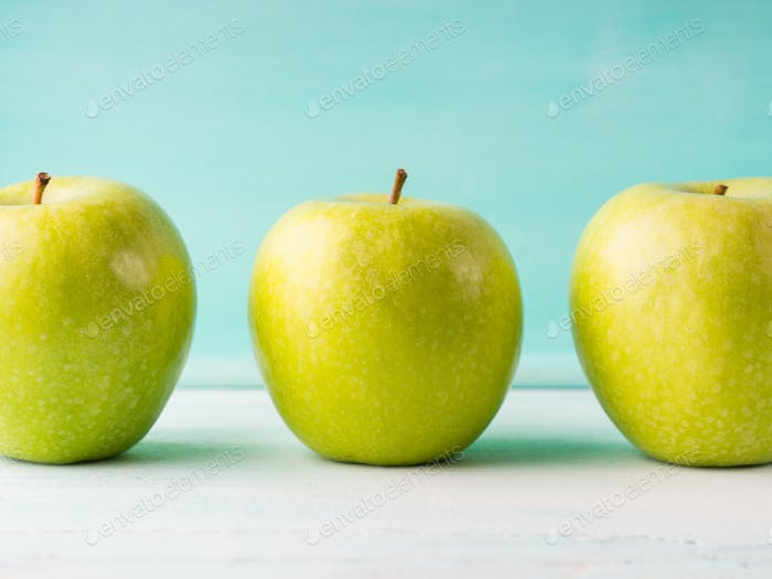 Three Green apples on turquoise background