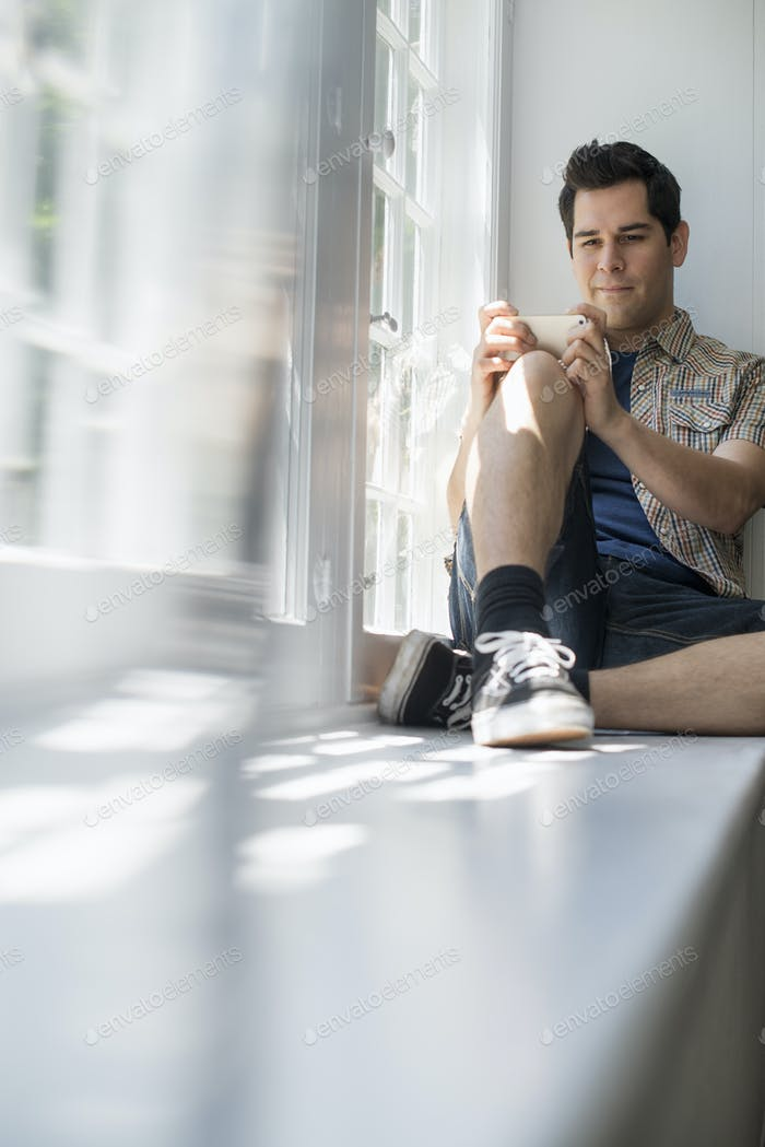 Man sitting by a window, holding a cell phone.