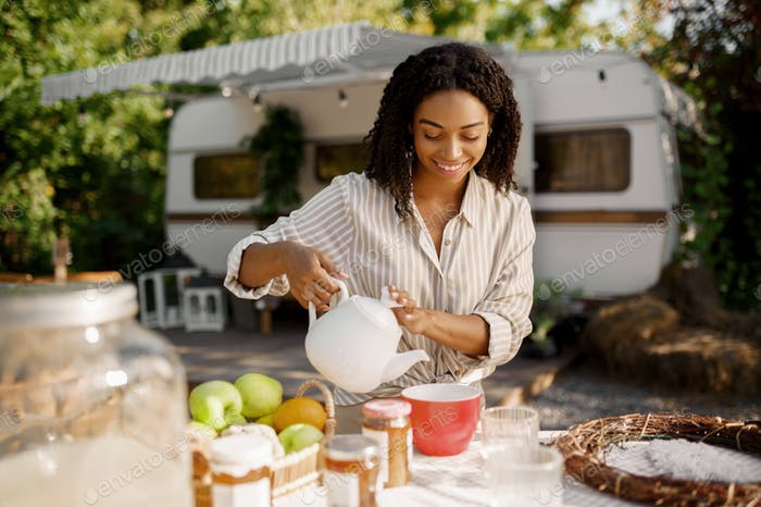 Female person cooking breakfast near rv, camping