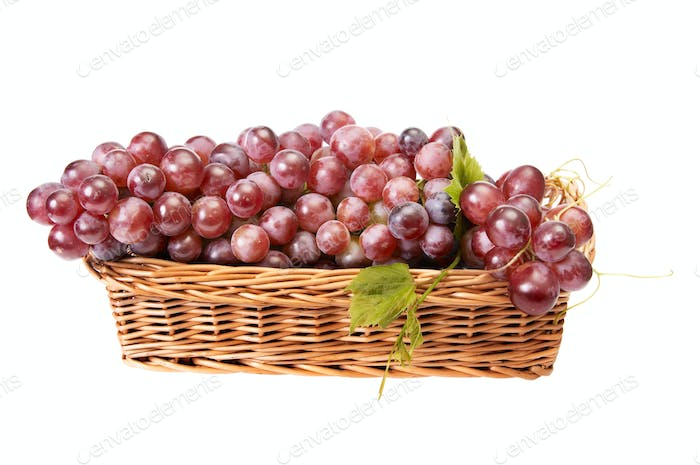 Wooden basket and ripe grapes on a white.