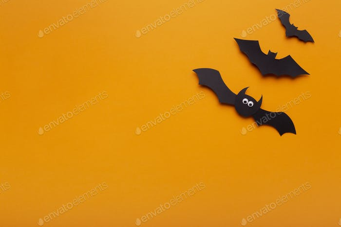 Black paper bats on orange background with copy space
