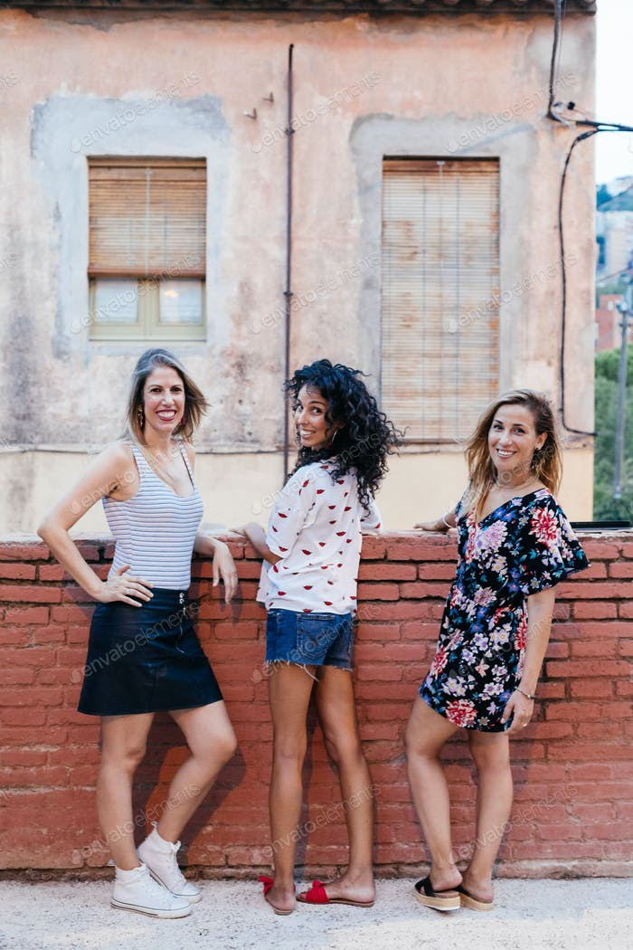 Three girls posing by a wall