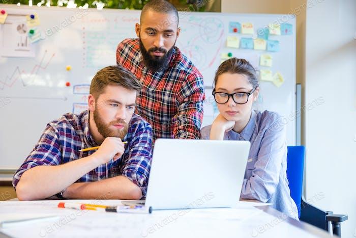 Fokussierte multiethnische Gruppe von Menschen, die mit Laptop zusammen arbeiten