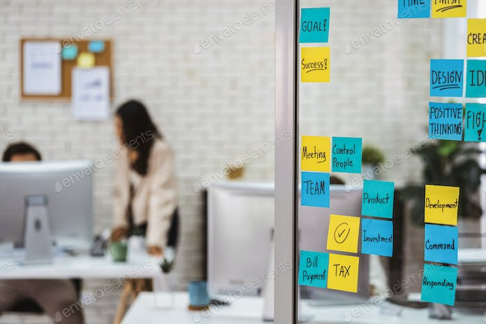 Various post it notes of business strategy wording over the glass wall in office or coworking space