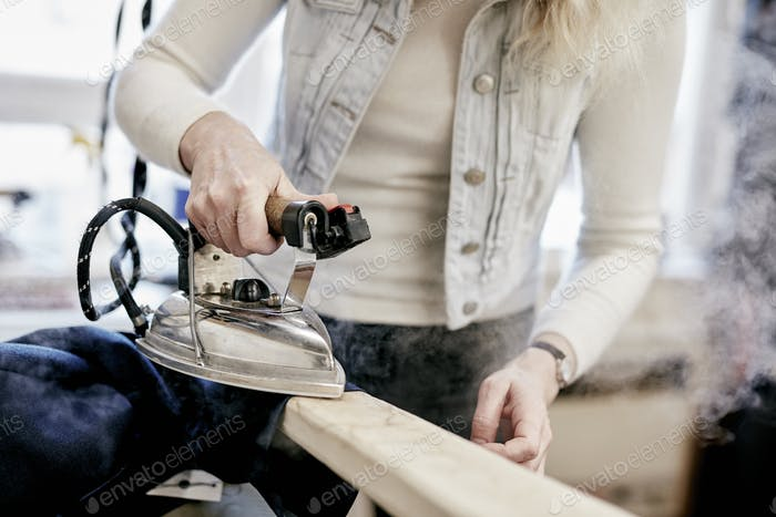 A woman using a steam iron on a new jacket, pressing the newly made garment.