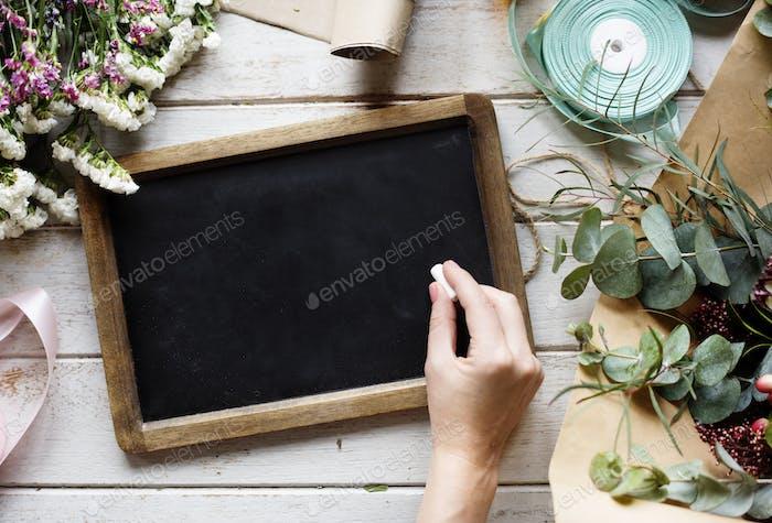 Handhaltend Kreide Schreiben auf blanko Design Space Black Board mit